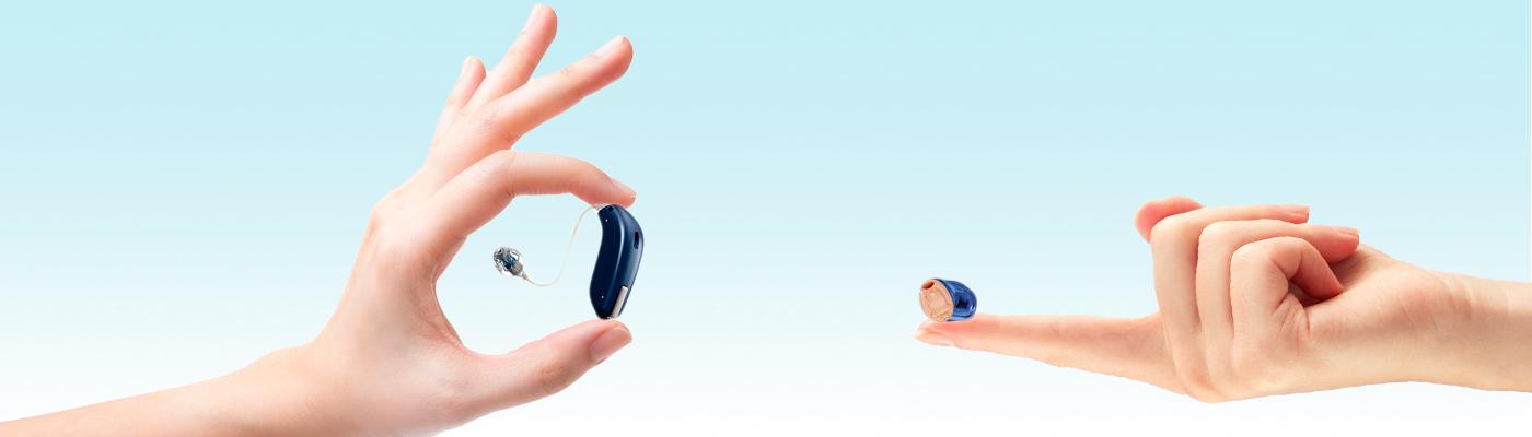 Zwei Hänge. Eine hält in IdO-Hörgerät, die andere ein HdO-Hörgerät.